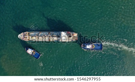 Aerial drone photo of industrial fuel and gas tanker being towed by tugboats in bay and shipyard of Elefsina, Attica, Greece #1546297955