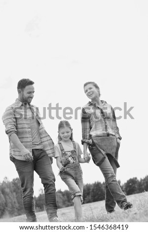 Black and white photo of Happy family walking in wheat field #1546368419