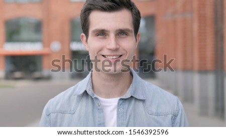 Portrait of Smiling Young Man Outside Building #1546392596