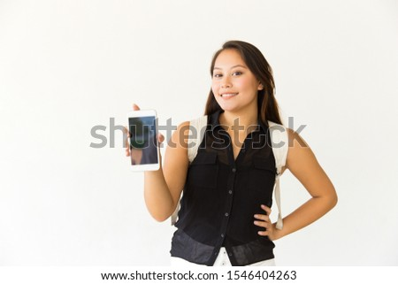 Happy woman showing smartphone with blank screen. Beautiful cheerful young woman holding cell phone with black screen and smiling at camera. Technology concept #1546404263