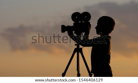 Little child silhouette with professional photo camera close sunset sky, early hobby