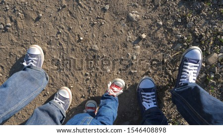 Baby child and parents feet with sneakers walk together on road, parental support, learning process, conceptual, unknown  future #1546408898