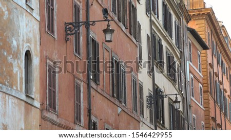 ROME, ITALY - OCTOBER 06, 2018: Detail of street lamp on colored wall building, travel in old Europe #1546429955