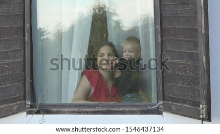 Mother and baby child looking out the window with shutters, outdoor view #1546437134