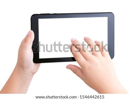 Top view closeup on the hands of a white child holding a black tablet PC with a white blank screen and scrolling the photos or Internet pages with his fingers. Child safety on the Internet. Copy space #1546442615
