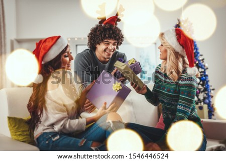 Cheerful young friends dressed in cozy warm sweaters are spending time in the living room on Christmas - New Year eve, smiling, having fun and giving Christmas presents to each other. #1546446524