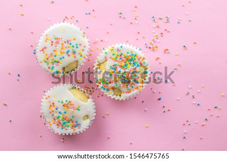 Three little white frosted white cupcakes in centre of pink background sprinkled with multi - coloured sprinkles on pink with copy space #1546475765