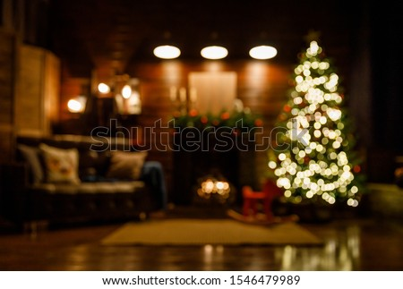 Christmas and New Year interior - blur background: fireplace, lamps, green Christmas tree, brown leather sofa, gifts, candles, moose rocking chair.  Lots of lights glowing in the dark. #1546479989