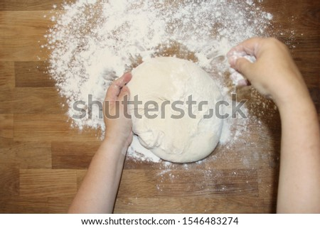 female hands knead the dough on a wooden table, sprinkled with flour, close-up, selective focus, home cooking concept, copy space #1546483274