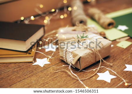 Hand made craft gifts of paper at Christmas holiday and small presents. On wooden background, Top view. Making New Year home decoration of scandinavian style and books Royalty-Free Stock Photo #1546506311