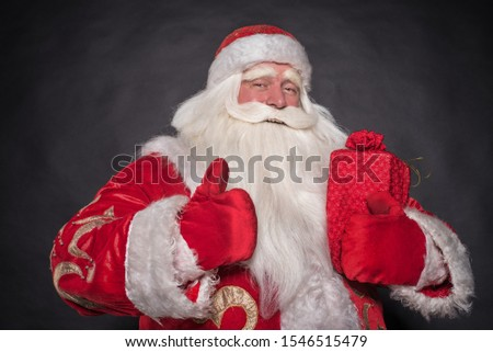 Santa Claus on a black background. The majestic and fabulous portrait of Santa Claus on a black background, who carefully and cunningly looks, smiles and laughs cheerfully and laughs. #1546515479