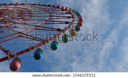 Looking upward to the colorful Ferris wheel in blue sky. #1546529312