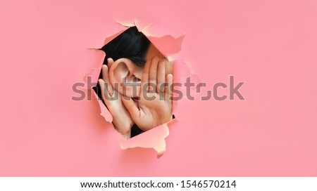 Female ear and hands close-up. Copy space. Torn paper, pink background. The concept of eavesdropping, espionage, gossip and the yellow press. Caricature with an enlarged ear. #1546570214