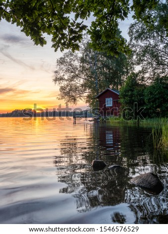 Picture of Lakeside Sunset with trees, scandinavian wooden house and blue sky