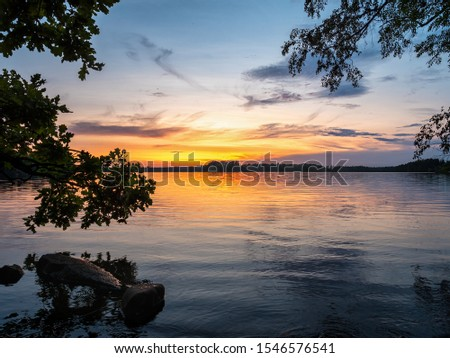 Picture of Lakeside Sunset with trees and blue sky