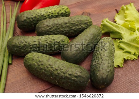 Cucumbers with lettuce and leek on a wooden table #1546620872