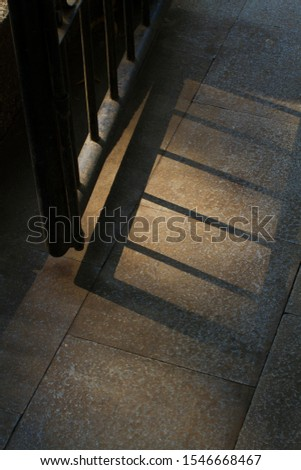 A photograph of park gate silhouette on the floor in the morning #1546668467