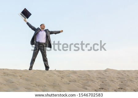 Businessman working and using a laptop and phone in a desert #1546702583