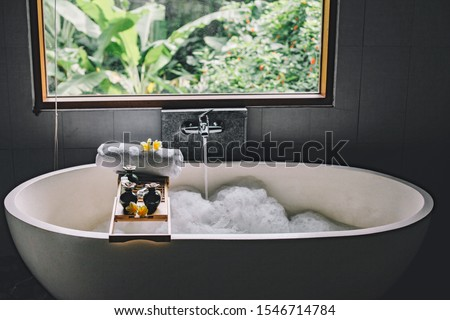 Beauty products on tray on bathtub by the window. Bath with foam is filling with water. Relaxing in Bali luxury spa hotel. #1546714784