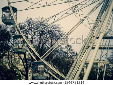 Front picture of huge ferris wheel in Brno, the Czech republic. Cross-processed coloured picture of ferris wheel with trees and sky on background. Focus on metal construction and cabins.