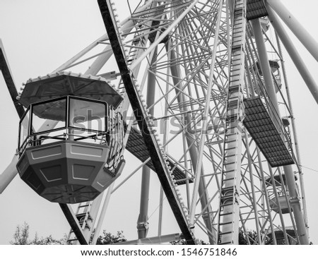 Side picture of huge ferris wheel in Brno, the Czech republic. Black and white picture of ferris wheel with focus on a single beautiful cabin. Huge metallic structure of entertaining attraction.
