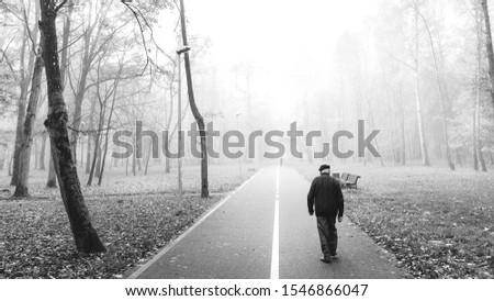 Walk the walk. Man walking through foggy morning city park. #1546866047