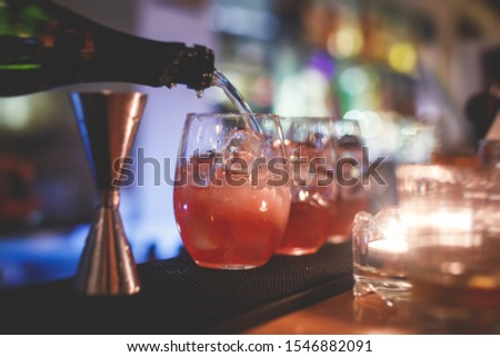 Beautiful row of different colored alcohol cocktails on a party, martini, vodka, and others on decorated catering bouquet table on open air event with bartender in the background #1546882091