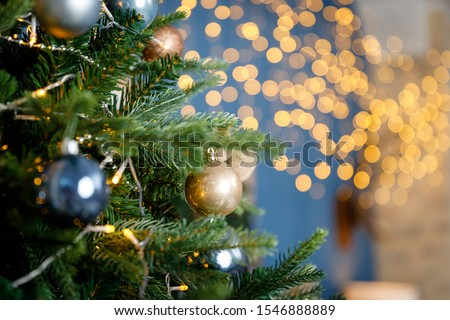 Modern design Christmas tree decorated with balls and garlands - navy blue, brown, beige. Winter holidays composition. Close up