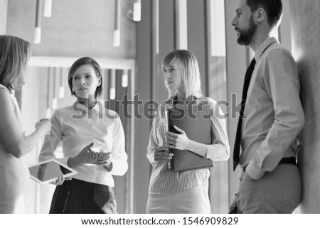 Black and white photo of business people discussing plans before meeting in office hall