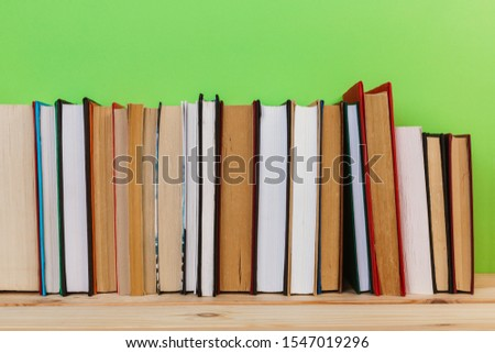 Simple Simple composition of many hardback books, unprocessed books on a wooden table and a green background. back to school. Copy space. Education. #1547019296