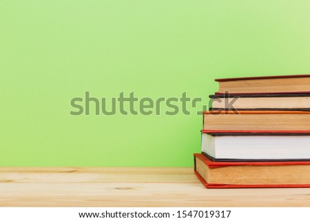 Simple Simple composition of many hardback books, unprocessed books on a wooden table and a green background. back to school. Copy space. Education. #1547019317