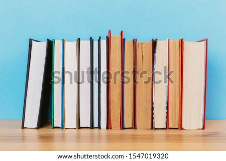 A simple composition of many hardback books, raw books on a wooden table and a bright blue background. Going back to school. Copy space. Education. #1547019320