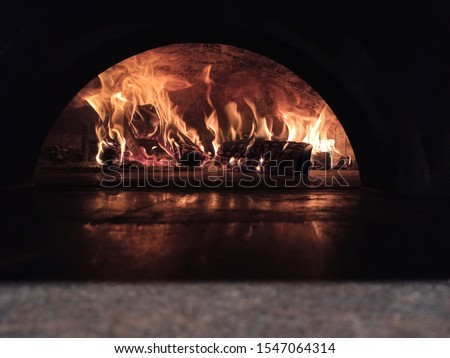 Fire wood burning in the oven. Italian pizzeria. Traditional Pizza oven. Authentic Italian oven. It was built by hand from naples earth. The original pizza oven with flame  inside. #1547064314