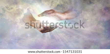 Let there Be Light Divine Concept -  God's hands emerging from beautiful clouds, cupped, with rainbow colored bright white star burst of light between and copy space  Royalty-Free Stock Photo #1547131031