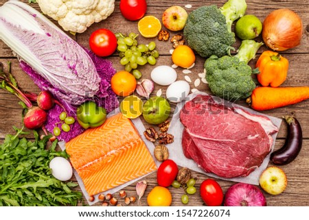 Trending paleo/pegan diet. Healthy balanced food concept. Set of fresh products, raw meat, salmon, vegetables and fruits. Old wooden boards background, top view #1547226074