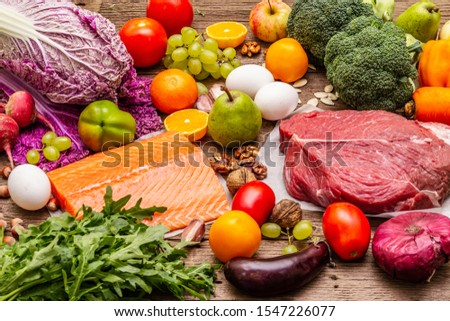 Trending paleo/pegan diet. Healthy balanced food concept. Set of fresh products, raw meat, salmon, vegetables and fruits. Old wooden boards background #1547226077