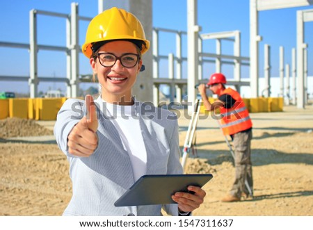 Happy beautiful female architect with tablet on construction site. She is smiling and satisfied with her job, giving thumb up looking at camera, behind her construction worker with measuring device #1547311637