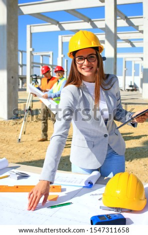 Happy beautiful female architect on construction site. She is smiling and satisfied with her job, behind her construction engineers planning and talking about the project, teamwork #1547311658