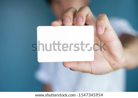 Hand holding  a blank piece of paper. Close up  white business card. #1547345954
