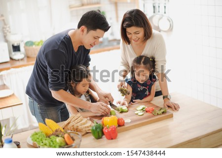 Young Asian love family are preparing the breakfast, sandwich vegetable on table in the kitchen which Excited smiling and felling happy. parent teach daughter to cooking food on the day at home. #1547438444