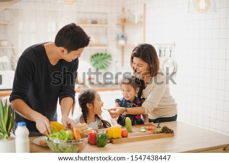 Young Asian love family are preparing the breakfast, sandwich vegetable on table in the kitchen which Excited smiling and felling happy. parent teach daughter to cooking food on the day at home.  #1547438447