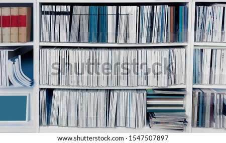 White bookcase with many reports, magazines or other publications #1547507897