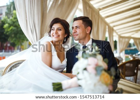 Young bride and groom in a cafe. Husband and wife hold each other's hands. Loving couple in a restaurant. Groom kissing a bride. Pretty bride and stylish groom. Wedding day. Marriage. #1547513714