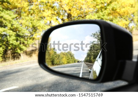 Closeup of car side rear view mirror on sunny day #1547515769