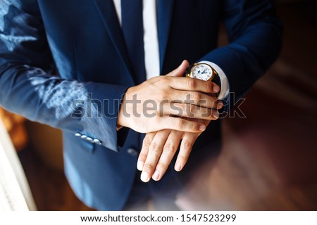 Men's wrist watch, the man is watching the time. Businessman clock, businessman checking time on his wristwatch. Groom's hands in a suit adjusting wristwatch, wedding preparations, groom accessories. #1547523299
