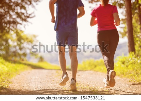 young happy couple enjoying in a healthy lifestyle while jogging on a country road through the beautiful sunny forest, exercise and fitness concept #1547533121