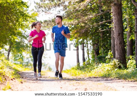 young happy couple enjoying in a healthy lifestyle while jogging on a country road through the beautiful sunny forest, exercise and fitness concept #1547533190