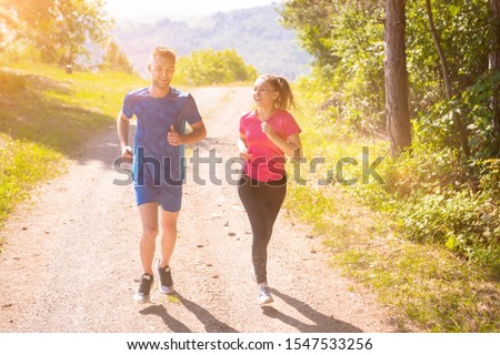 young happy couple enjoying in a healthy lifestyle while jogging on a country road through the beautiful sunny forest, exercise and fitness concept #1547533256