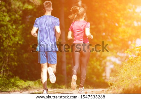 young happy couple enjoying in a healthy lifestyle while jogging on a country road through the beautiful sunny forest, exercise and fitness concept #1547533268