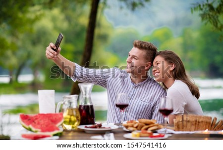 young happy couple taking selfie while having picnic french dinner party outdoor during summer holiday vacation  near the river at beautiful nature